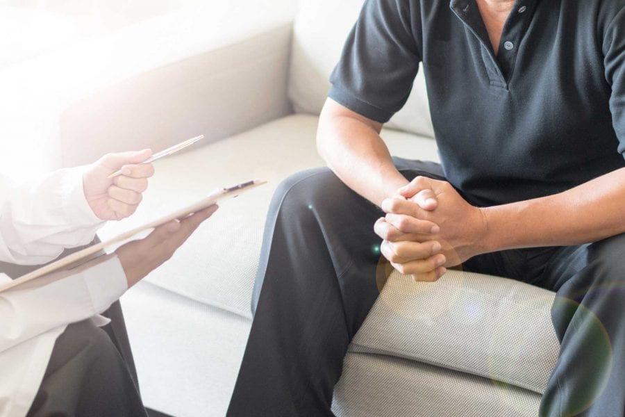 doctor talking to patient on couch