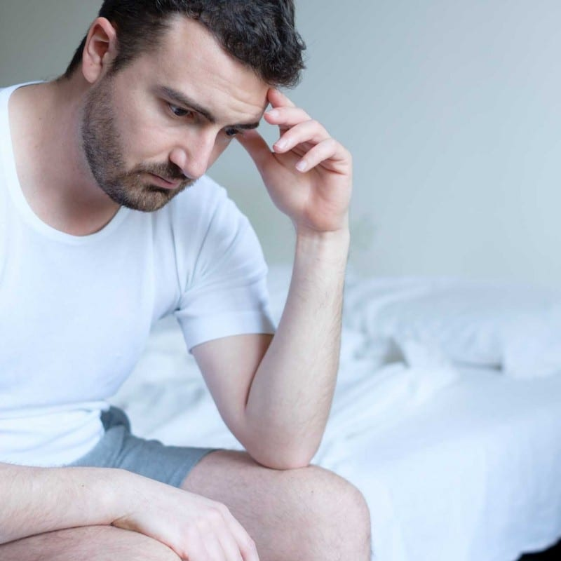 sad man sitting on edge of bed